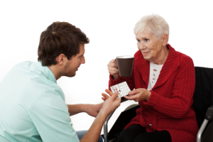 caregiver giving medicine to an elderly woman